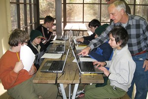Professor Randy Cooper, far right, teaches Boy Scouts from Troop 839 how to use laptop computers borrowed from UH Bauer College during a winter camp in January.