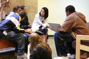 Finance and accounting junior Kim Pham, center, mentors a group of Houston-area high school students during the January kickoff of the Game of Real Life, a program that encourages teenagers to pursue a college education.