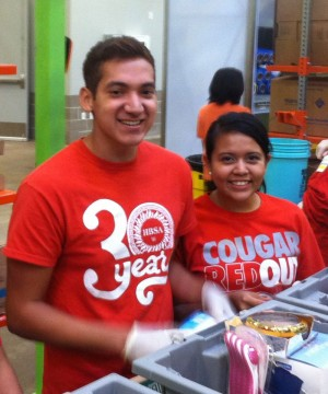 Two representatives from the Hispanic Business Student Association volunteer time at the Houston Food Bank.