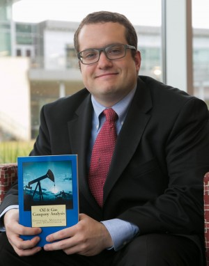 Alfonso Colombano holds his first book, Oil and Gas Company Analysis, which analyzes more than 30 oil and gas companies.